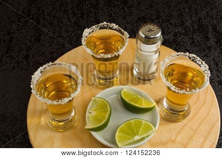 Three shots of gold tequila with lime and salt on the black background. Tequila shot. Gold Mexican tequila. Tequila
