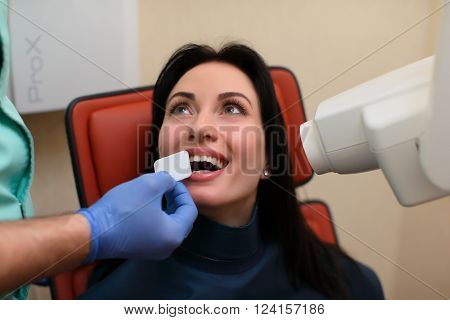 female patient mouth and assistant directing x-ray machine at dental clinic