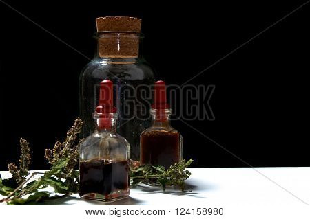 Three Glass Bottles With Herbal Extracts And Dried Herbs At Eye Level
