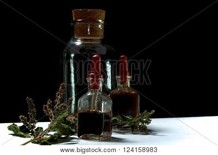 Three Glass Bottles With Herbal Extracts And Dried Herbs Close Together