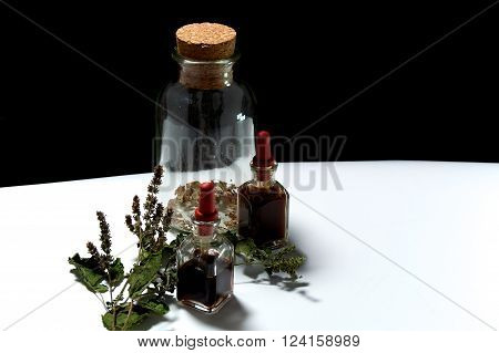 Three Glass Bottles With Herbal Extracts And Dried Herbs From Above