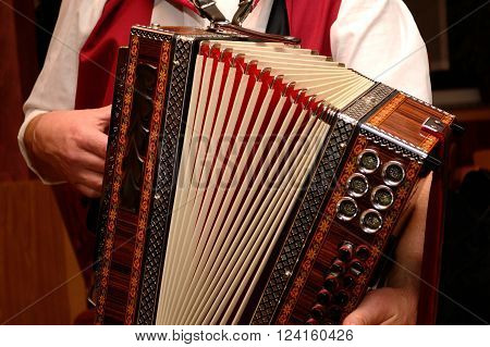 Man in costume plays on a Styrian harmonica - close-up