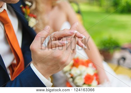 Man's and woman's hands. Bride and groom holding hands together bouquet in background focus on hand. Ring on hand. Man in suit shirt and orange tie. Color of tie is same as flowers in bouquet.