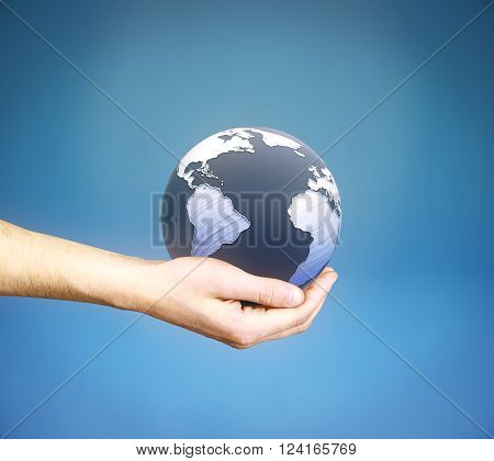 Male hand holding 3D rendered terrestrial globe on blue background