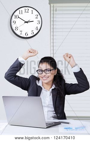 Happy Indian businesswoman raises hands up in the office with a laptop on desk celebrating her success