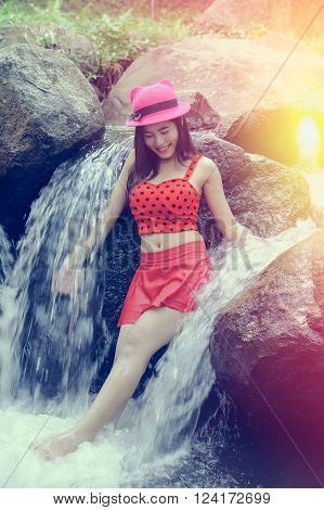 Asia beautiful young sexy girl posing on a rock in water fall