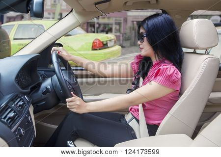 Successful young woman driving a new car while wearing sun glasses on the road