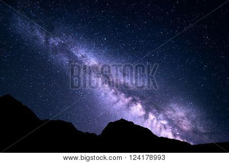 Mountain landscape with purple Milky Way. Beautiful night sky with stars and rocks at summer. Universe