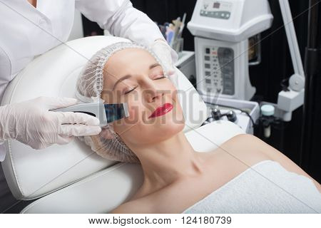 Close up of arms of beautician making laser treatment on female face. The woman is lying and smiling. Her eyes are closed with pleasure poster