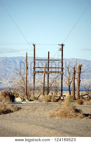 A radio mast and telephone pole standing in the desert at the Salton Sea in the ghost town of Salton City.