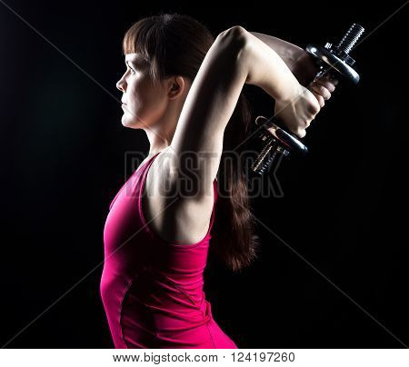 Woman doing exercise with weights on black background