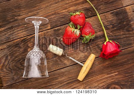 Objects used in romance. A rose, strawberries, a wine glass, and a cork and corkscrew make up for a romance concept image. poster