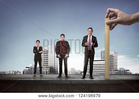 Hand holding wooden ruler mesuring employee performance. Working appraisal concept