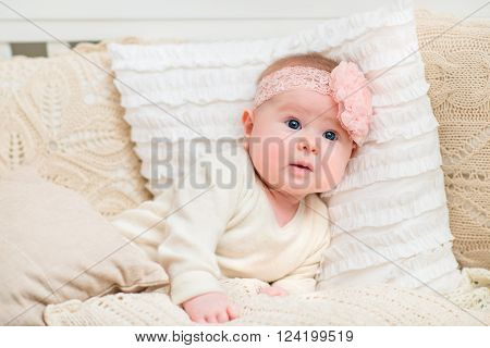 Surprised beautiful baby girl with chubby cheeks and big blue eyes wearing white clothes and pink band with flower lying on bed with knitted pillows. Babyhood and childhood concept