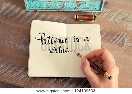 Retro effect and toned image of a woman hand writing on a notebook. Handwritten quote Patience is a Virtue as inspirational concept image
