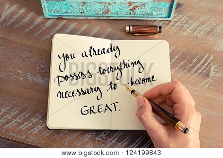 Retro effect and toned image of a woman hand writing on a notebook. Handwritten quote You already possess everything necessary to become great as inspirational concept image