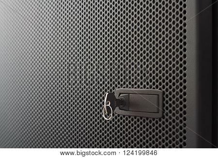 Black metallic door of server rack cabinet. The key is inserted into the door lock. Side lighting and shallow DOF