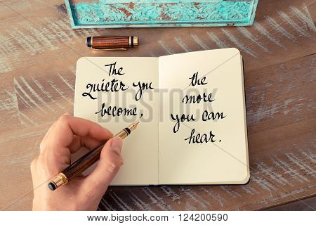 Retro effect and toned image of a woman hand writing on a notebook. Handwritten quote The quieter you become, the more you can hear as inspirational concept image