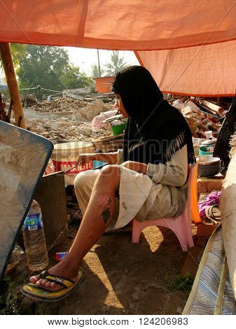 JAVA INDONESIA - June 19 2006: A young injured orphaned earthquake survivor cooks her evening meal in the rubble of her family house after the Yogyakarta Earthquake on June 19 2006 in Yogyakarta Province Java Indonesia.