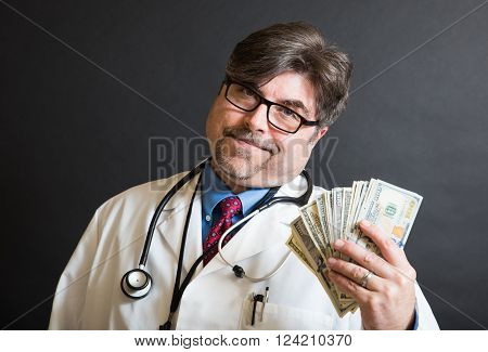 Doctor holding up a large amount of cash