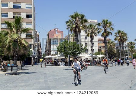 SPAIN, BARCELONA, JUNE, 27, 2015 - Passeig Maritim  on the seaside in Barcelona. A pleasant walk of tourists and locals on bike at Barceloneta beach in Barcelona, Catalonia, Spain