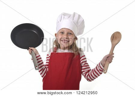 6 or 7 years old little girl in cooking hat and red apron playing cook smiling happy holding pan and spoon isolated on white background looking excited