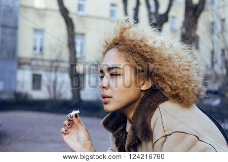 young pretty girl teenage outside smoking cigarette close up, looking like real junky, social issues concept
