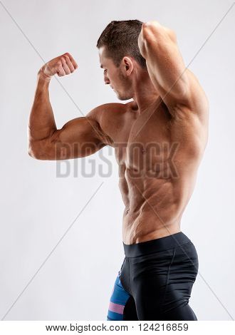 Bodybuilder Man Posing, Showing Perfect Abs, Houlders, Biceps, Triceps, Chest