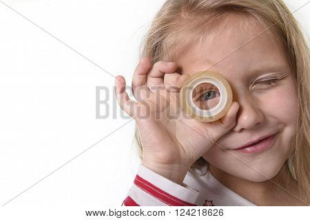 sweet beautiful female child 6 to 8 years old with cute blonde hair and blue eyes holding adhesive transparent tape isolated on white in education and primary or junior school supplies concept ** Note: Soft Focus at 100%, best at smaller sizes