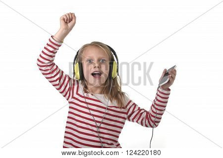 sweet little girl 7 years old with blonde hair and blue eyes listening to music with headphones and mobile phone singing and dancing happy isolated on white background