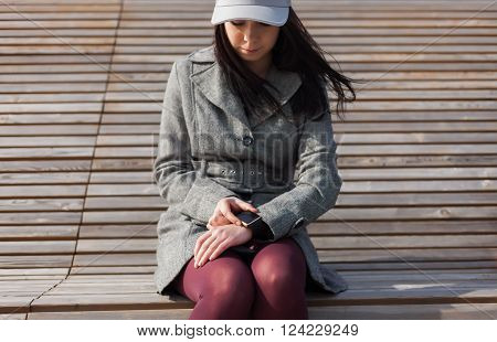 Young woman in grey hipster coat with smart watch outdoors ** Note: Shallow depth of field
