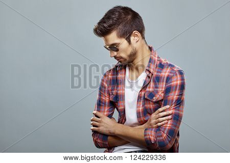 Handsome man with sunglasses and nice hairstyle posing in the studio on a light gray background