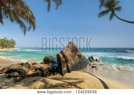 Stones and palm trees on a sandy beach of Hikkaduwa in Sri Lanka. Hikkaduwa is a small town on the south coast of Sri Lanka located in the Southern Province about 17 km north-west of Galle and 98 km south of Colombo.