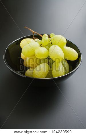 Bunch of fresh ripe juicy grapes placed in black ceramic bowl on neutral gradient background