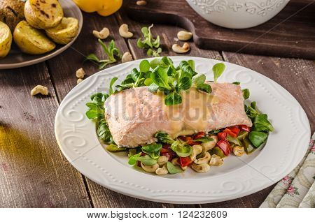 Salmon with hollandaise sauce and fresh salad with roasted walnuts