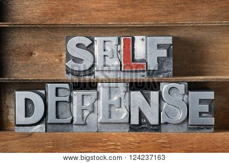 self defense phrase made from metallic letterpress type on wooden tray