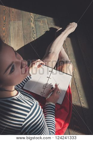 Cozy Photo Of Young Woman Writing In Notebook Sitting On The Floor