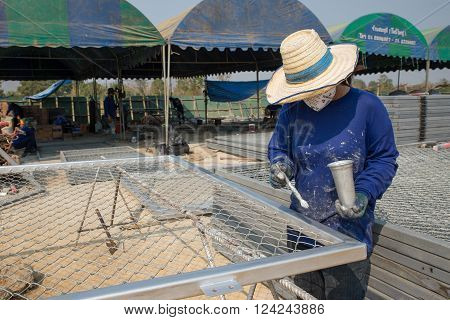 One Woman Paints Wire Metal Fence In Silver Color