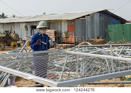 Petchaburi, Thailand - February 20, 2016: One woman worker paints wire metal fence in silver color at prepared area of outdoor construction on February 20, 2016 in Petchaburi, Thailand