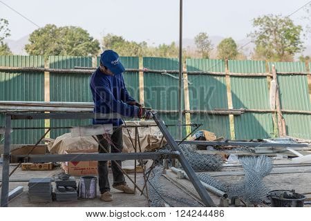 Petchaburi, Thailand - February 20, 2016: One man worker cut iron frame for making fence at prepared area for construction on February 20, 2016 in Petchaburi, Thailand