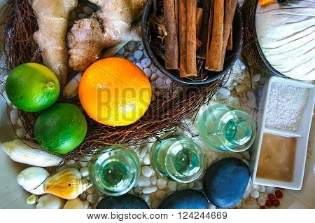 Top flat view of spa ingredients: oil in glass jars, orange, lyme, ginger, cinnamon sticks, stones, sand. Spa concept