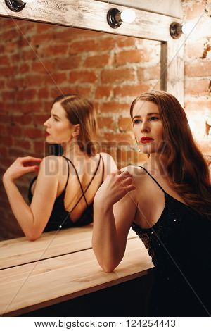 Seductive Woman in Black Dress Standing by Vintage Mirror with Bulbs in Dressing Room