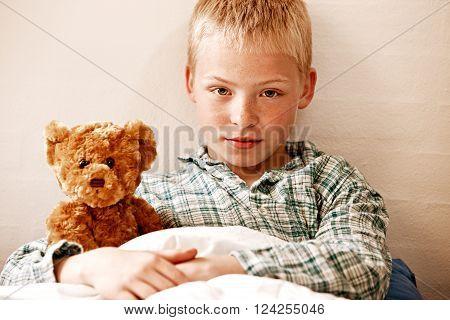 Insecure Young Boy Cuddling His Teddy Bear