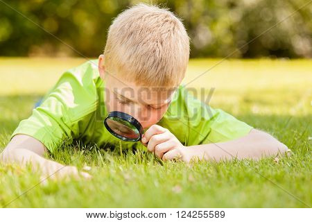 Child Looking Through Magnifying Glass On Ground