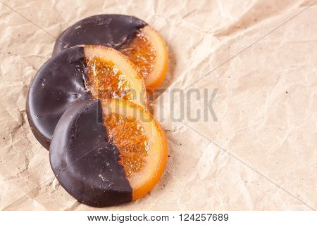 slices of orange coated chocolate on a paperbag