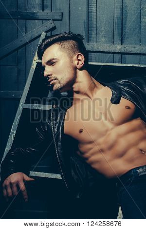 Handsome sexy muscular stylish young man in leather jacket with bare torso sitting indoor near stairs on wooden background vertical picture poster