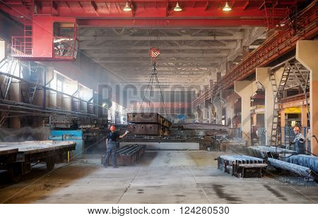 Tyumen, Russia - August 13, 2013: Finished goods warehouse at Concrete Goods Plant No. 5. Transportation of products in workshop by crane