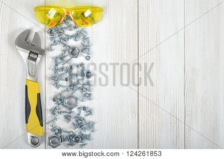 Top view of construction instruments and tools on wooden DIY workbench with open space on top. Wrench, glasses, nuts and screws.