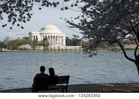 WASHINTON,DC - MARCH 25, 2016: Silhouette of a couple on a bench near the Jefferson Memorial during the Washington DC Cherry Blossom Festival