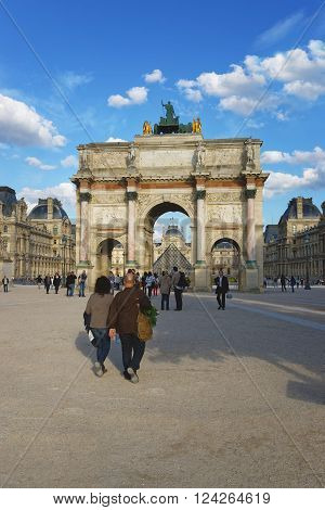 PARIS FRANCE - MAY 3 2012: Triumphal Arch and Louvre Palace in Paris in France. This triumphal arch is located in the Place of Carrousel. Louvre Palace is a former royal palace and now is a museum